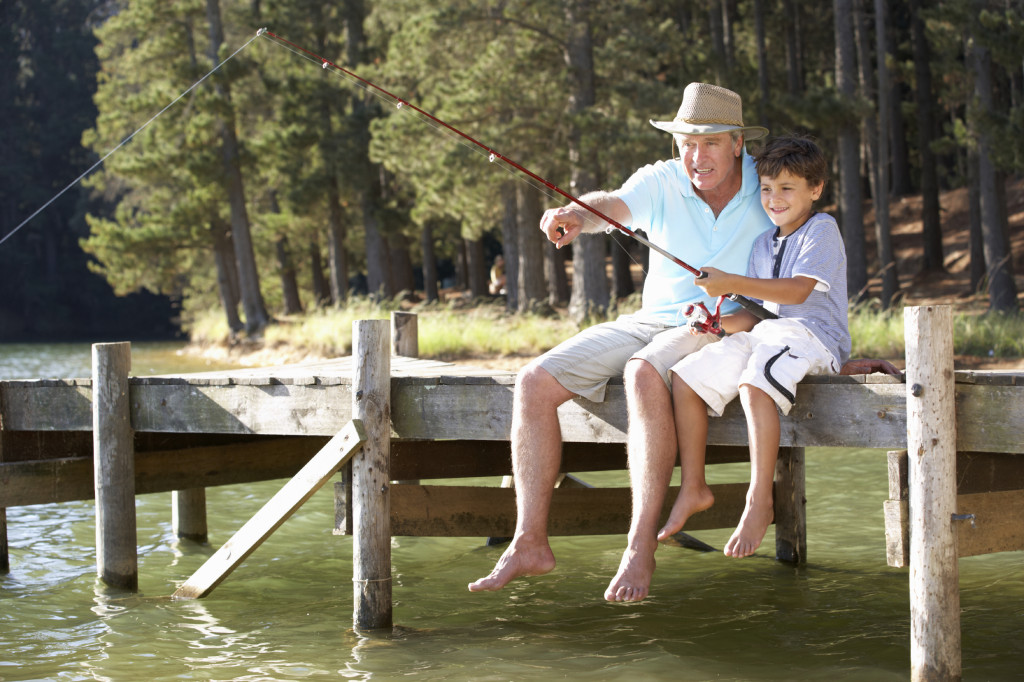 Senior man fishing with grandson