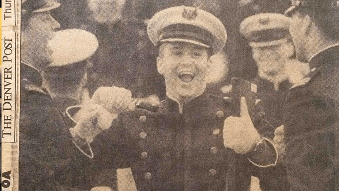 Sepia photo of a young man in uniform smiling with a thumbs-up